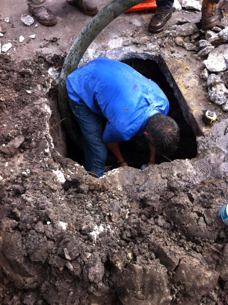 Down in a hole finding a broken pvc pipe leak